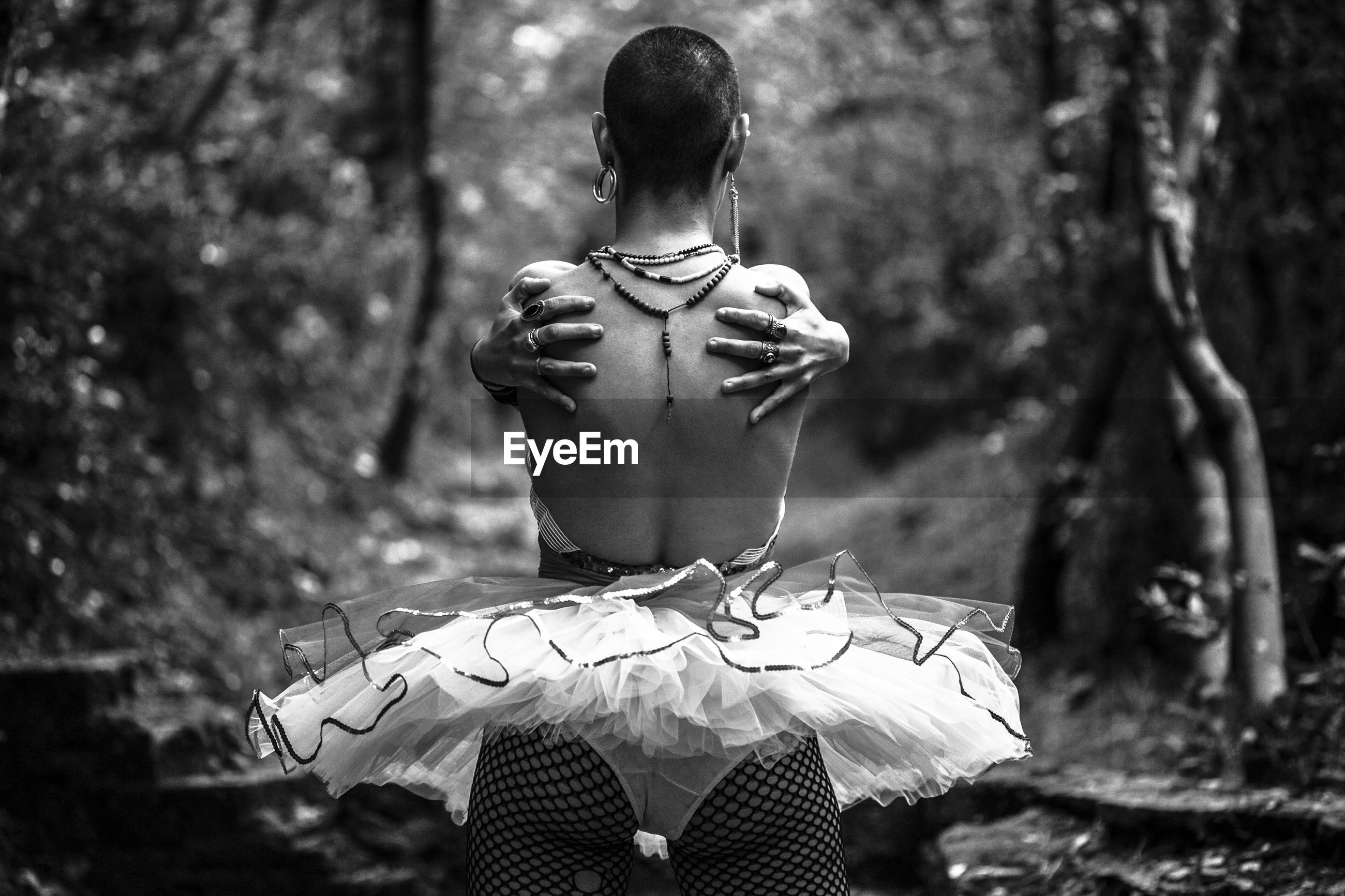 Rear view of shirtless young woman dancing in forest