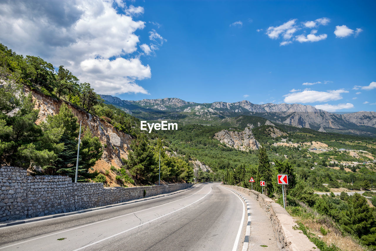 road, mountain, sky, cloud - sky, transportation, the way forward, direction, scenics - nature, beauty in nature, sign, plant, nature, mountain range, non-urban scene, symbol, day, tranquil scene, tree, tranquility, marking, diminishing perspective, no people, outdoors, dividing line, formation