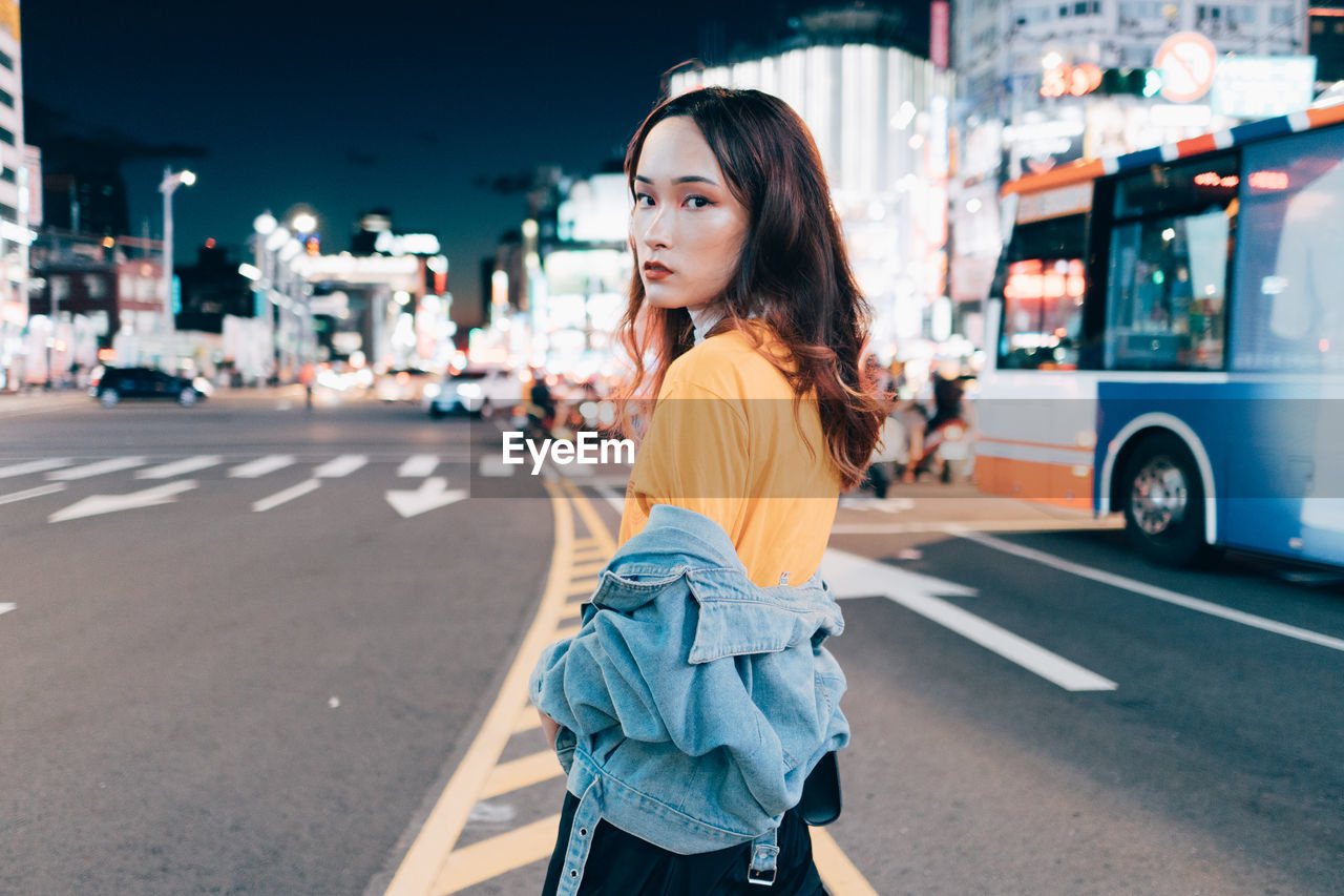 city, one person, transportation, mode of transportation, street, road, real people, land vehicle, focus on foreground, architecture, lifestyles, casual clothing, motor vehicle, young adult, car, young women, three quarter length, looking away, standing, hairstyle, hair, beautiful woman, outdoors