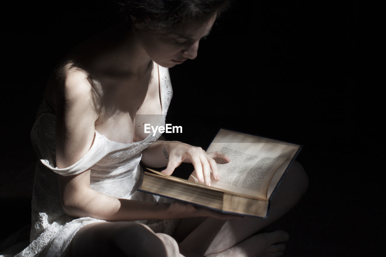 Woman Reading Book While Sitting Over Black Background