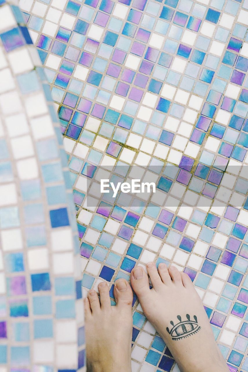 Low section of woman with tattoo on foot standing on tiled floor at poolside
