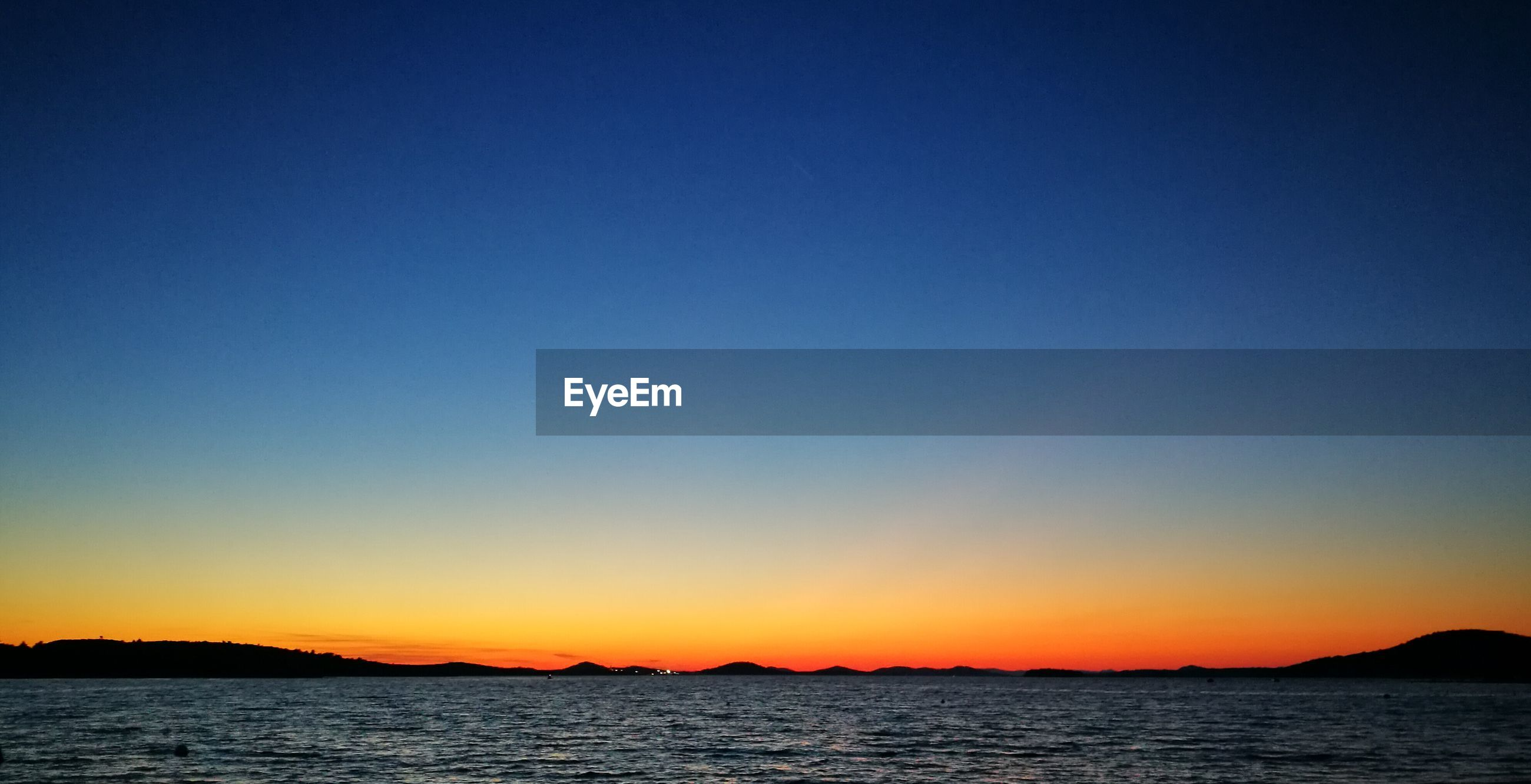 SCENIC VIEW OF SEA AGAINST CLEAR BLUE SKY DURING SUNSET
