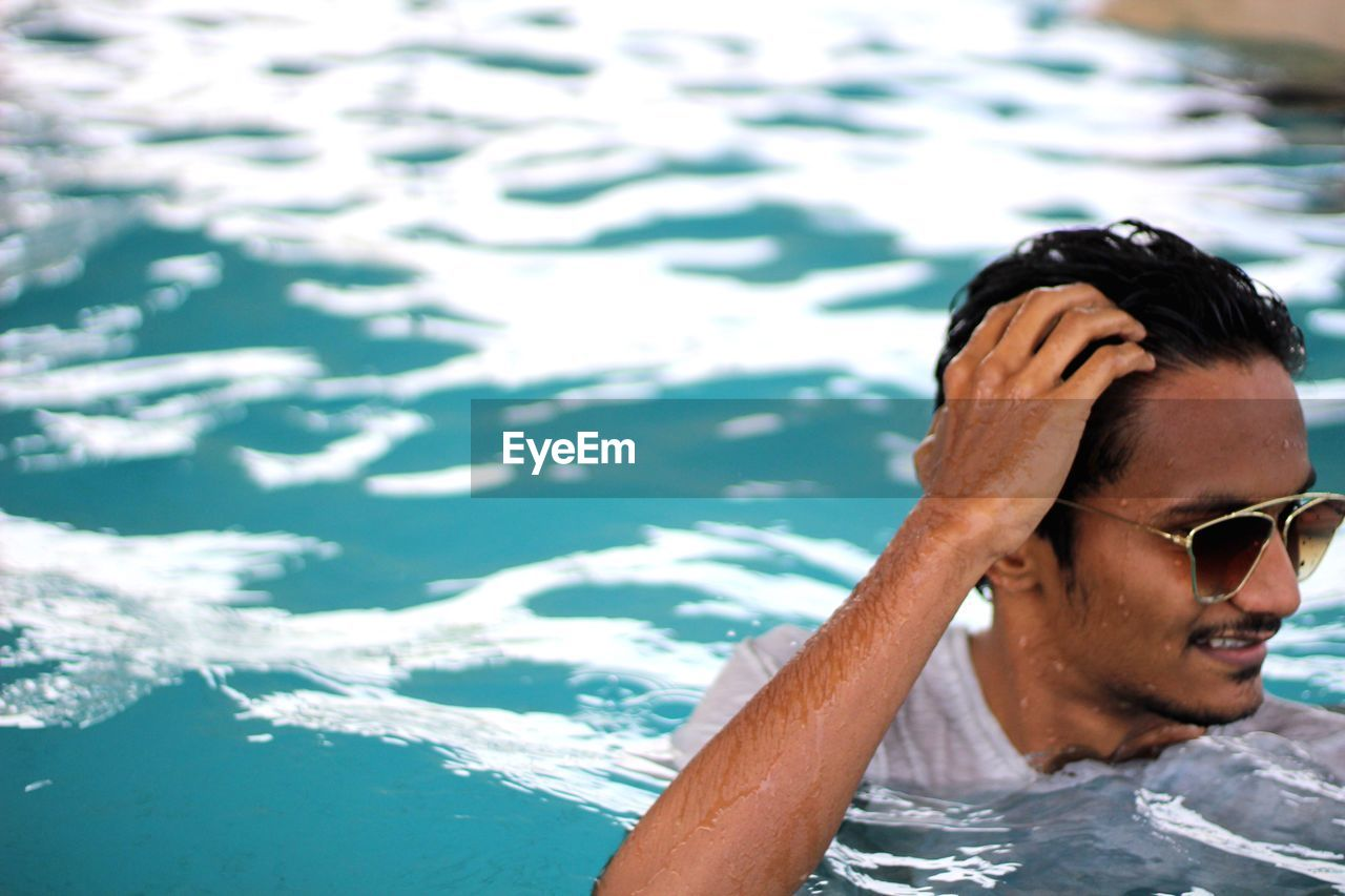Close-up of young woman wearing sunglasses in swimming pool