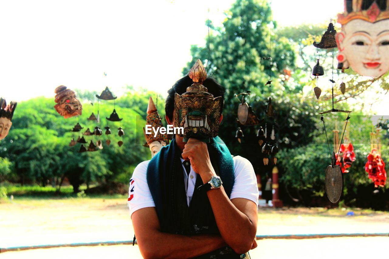 Man Holding Mask Against Sky