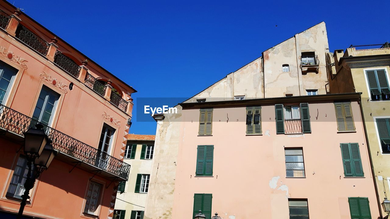 building exterior, architecture, built structure, low angle view, clear sky, window, outdoors, day, blue, balcony, residential building, no people, sky