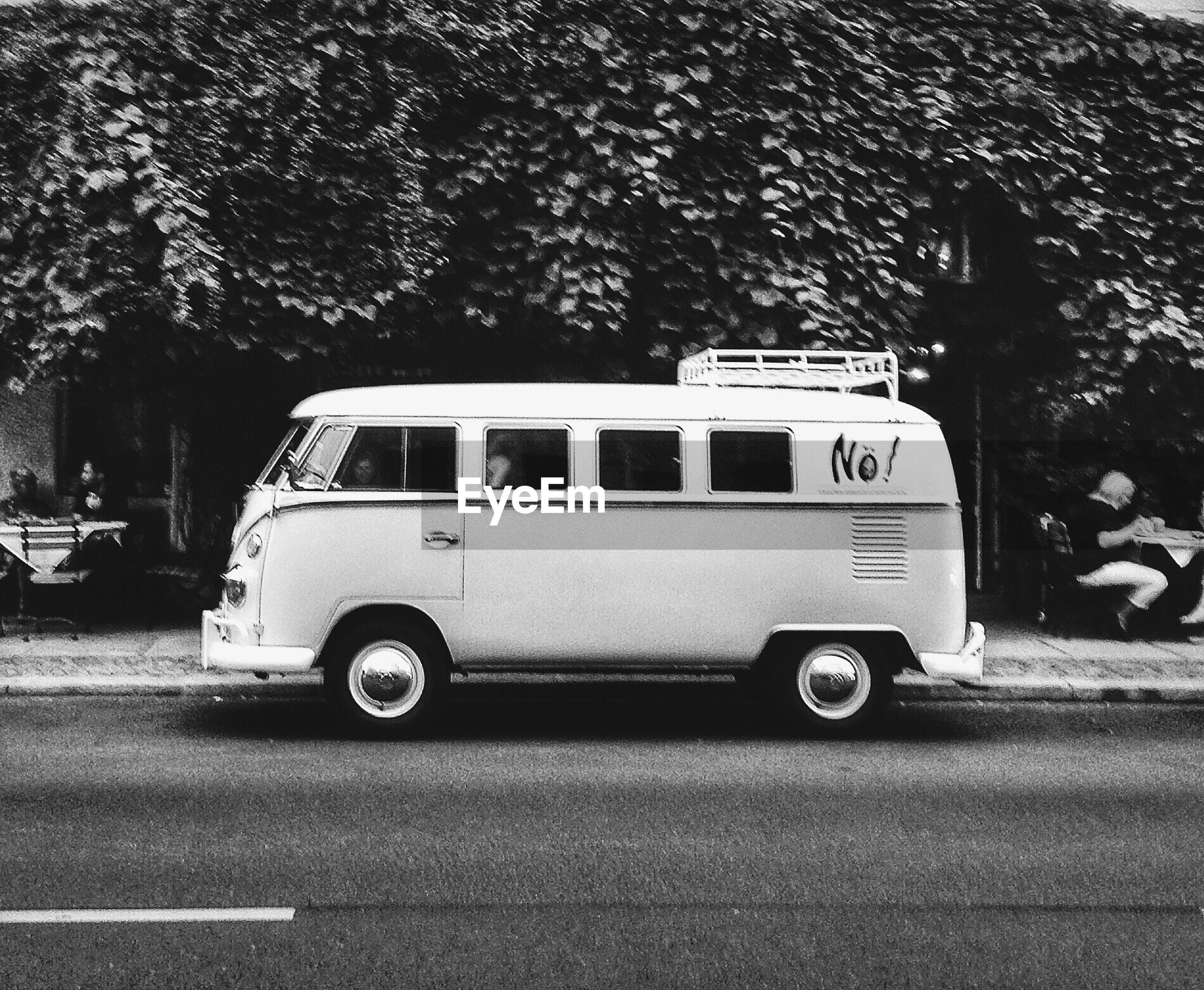 Van on road against trees
