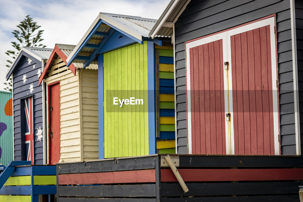 architecture, built structure, building exterior, multi colored, building, day, beach hut, house, no people, hut, residential district, closed, outdoors, nature, yellow, window, side by side, wood - material, sky, wall - building feature, garage