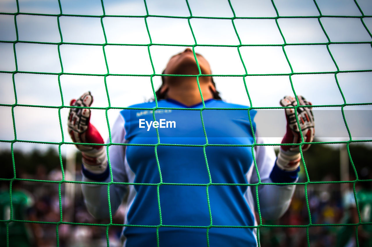 Low Angle View Of Woman Seen Through Net At Soccer Field