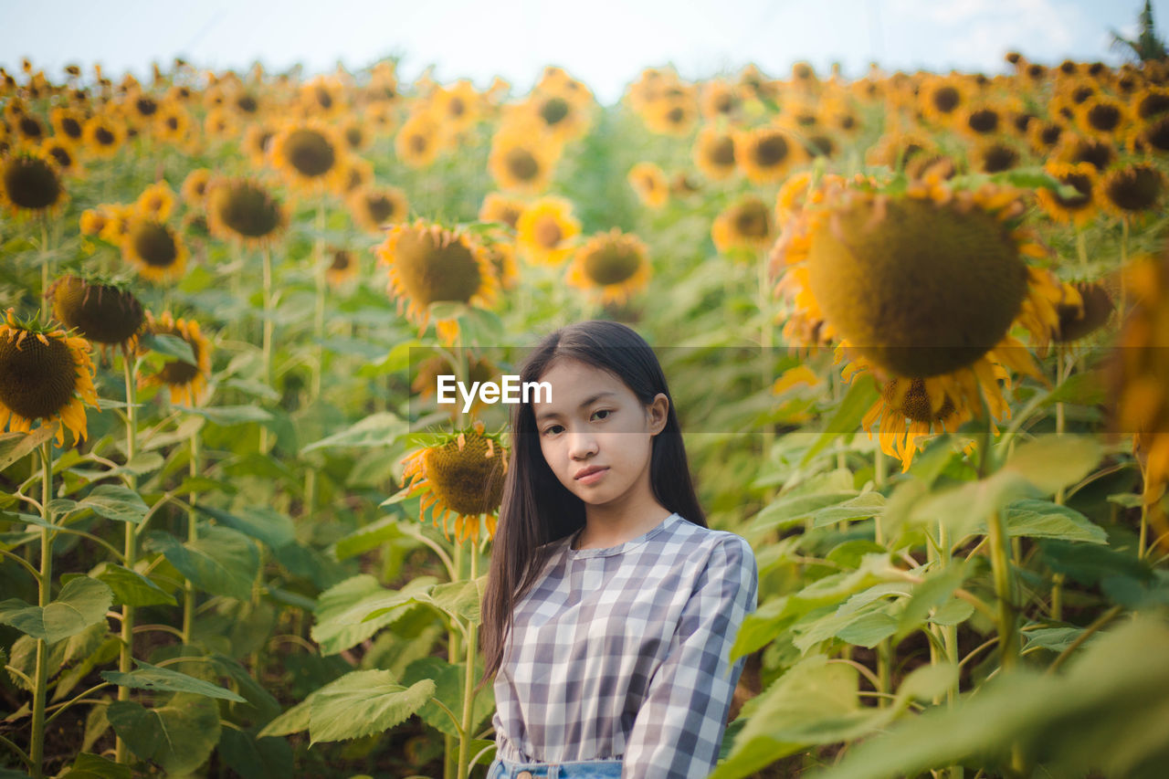 Portrait Of Young Woman Standing At Sunflower Farm