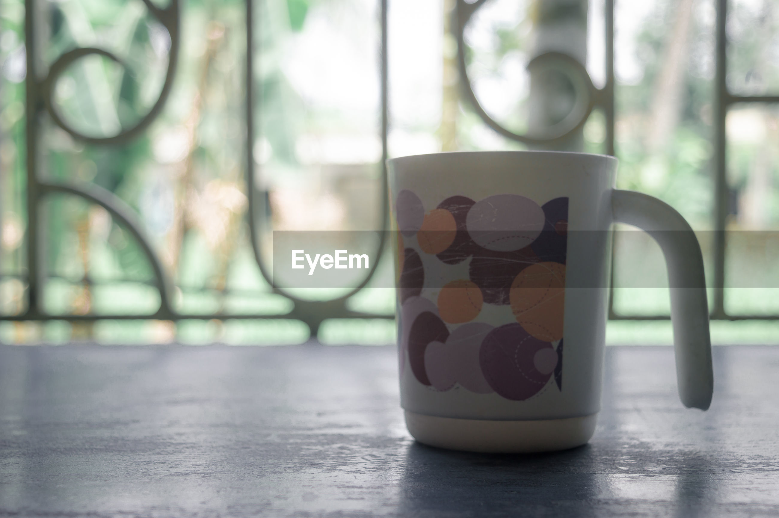 CLOSE-UP OF COFFEE CUP ON TABLE AGAINST WINDOW