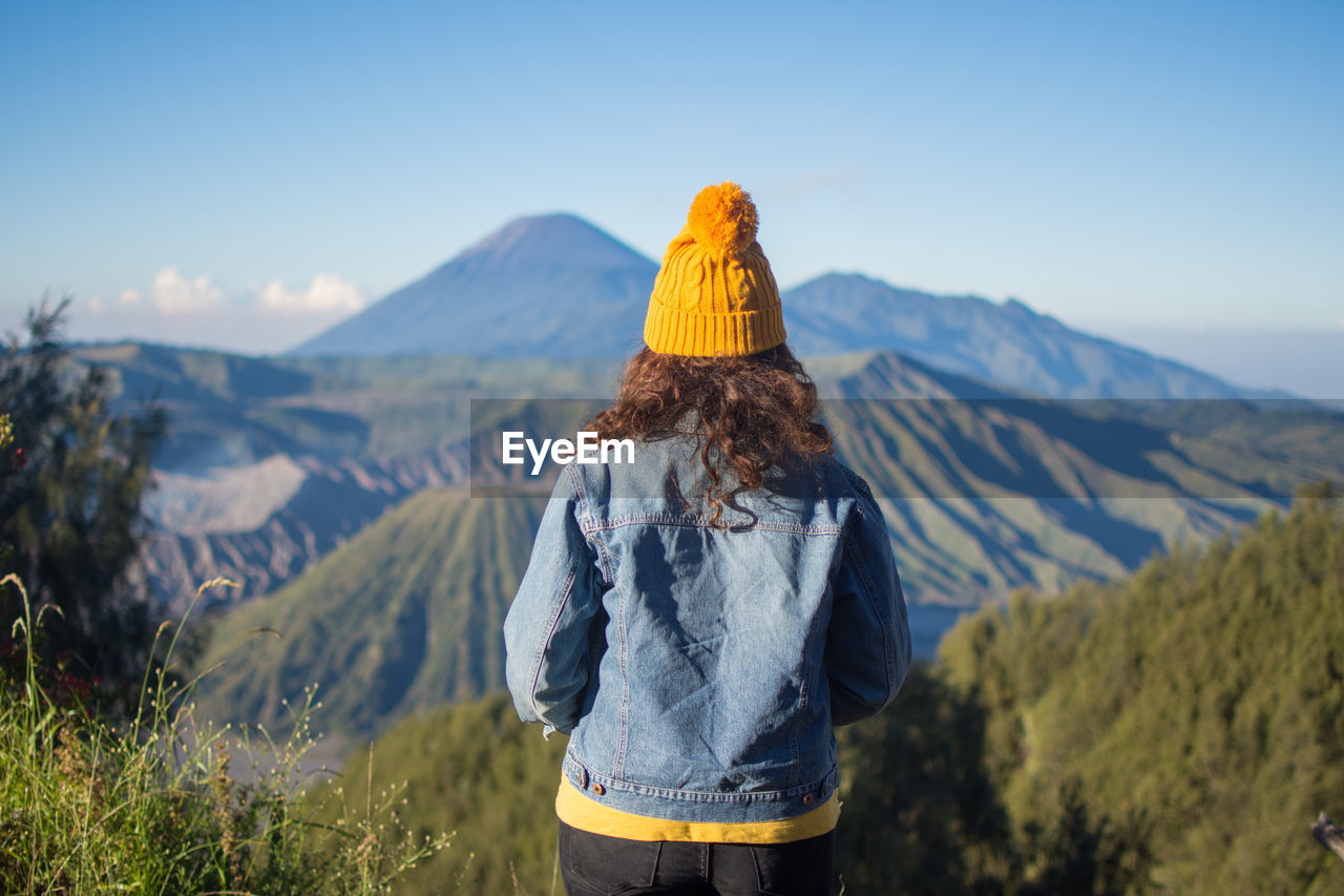 Rear view of woman wearing knit hat and denim jacket while standing on mountain against sky