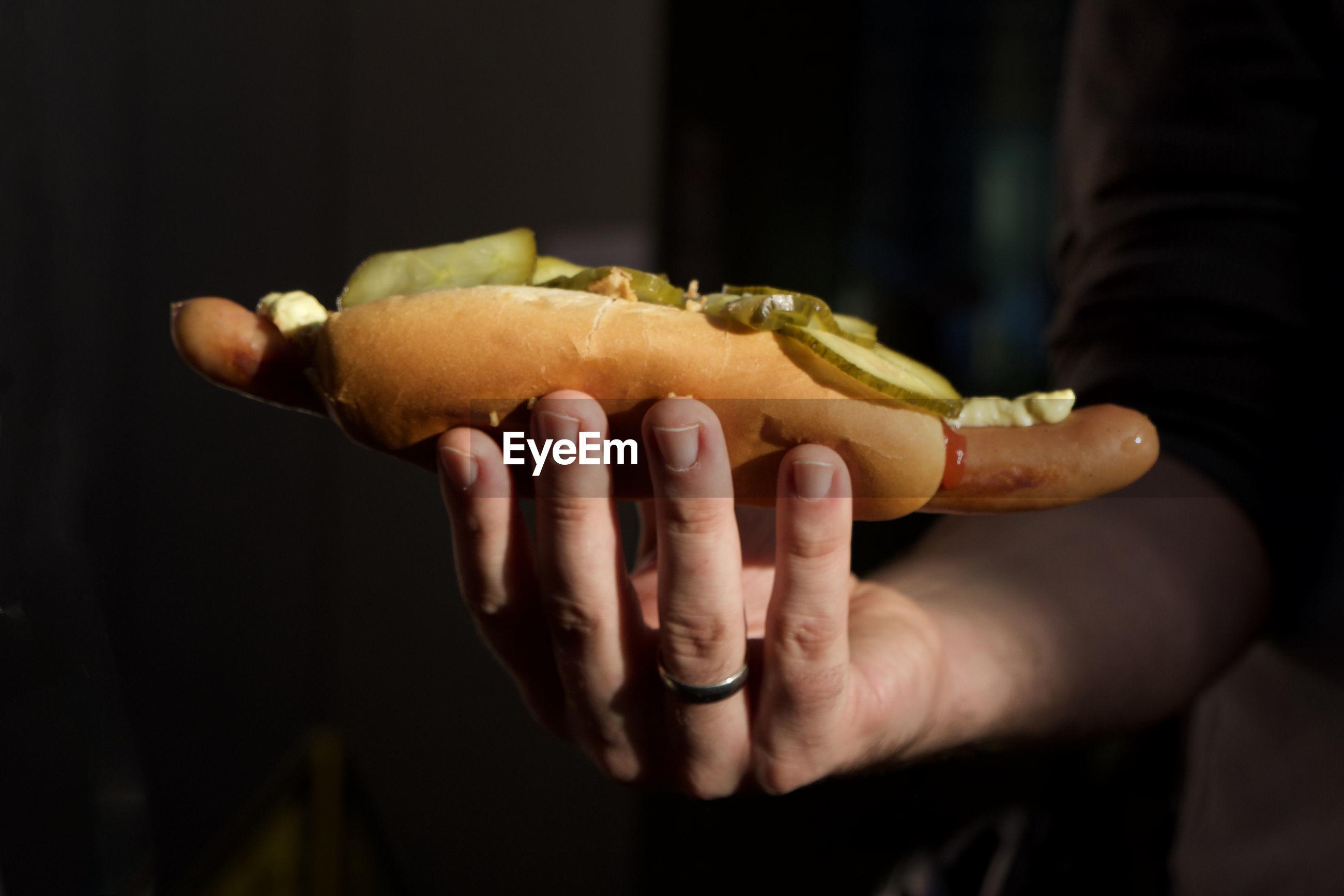 Close-up of hand holding hot dog