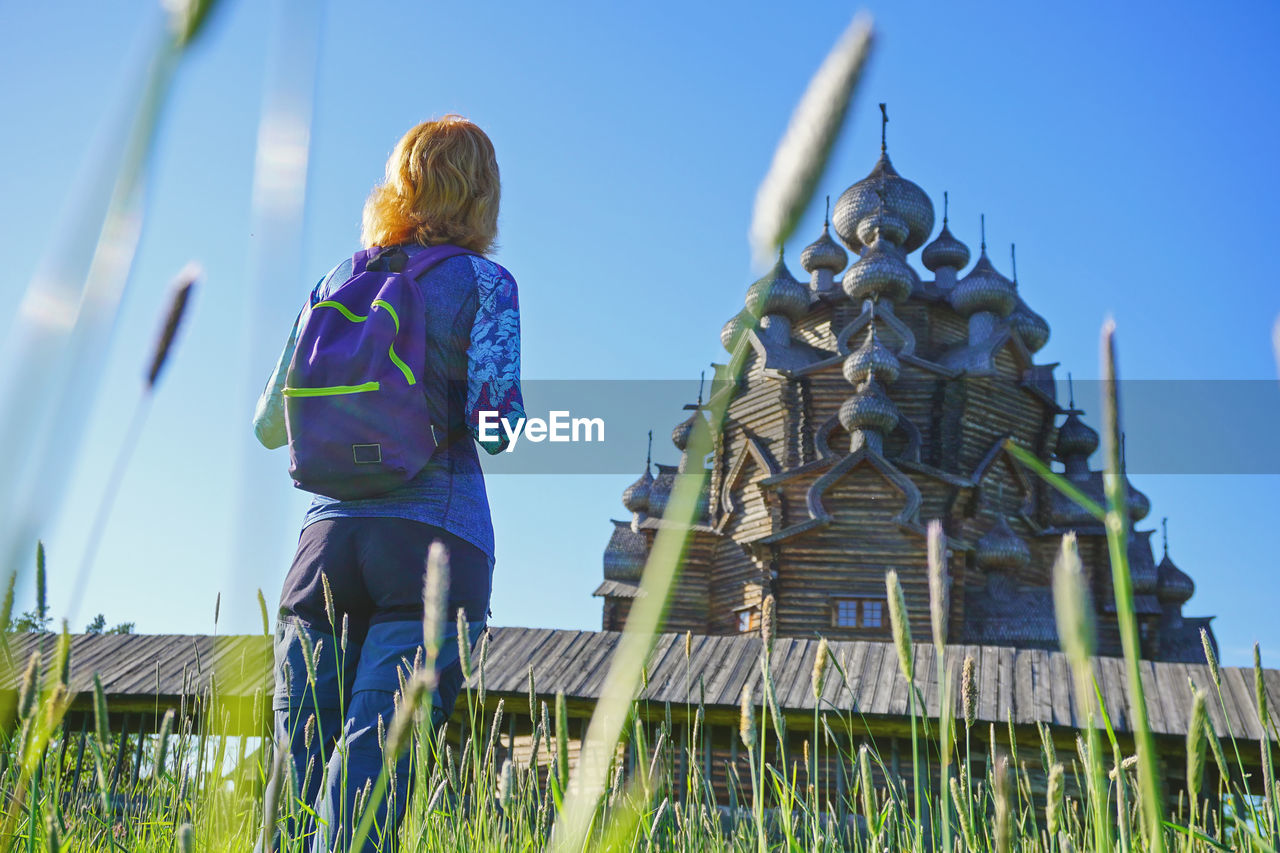 Rear view of woman looking at temple against blue sky