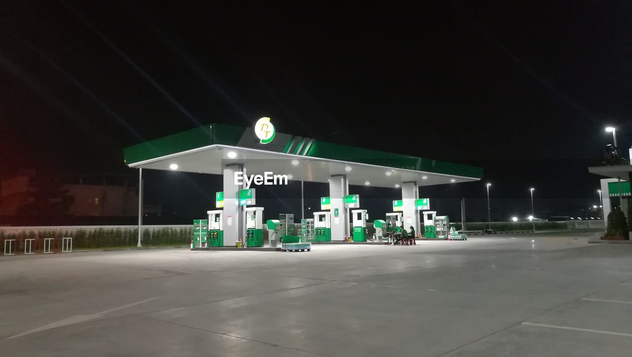 night, illuminated, gas station, fuel pump, fuel and power generation, refueling, fossil fuel, green color, gasoline, built structure, oil industry, building exterior, no people, outdoors, architecture