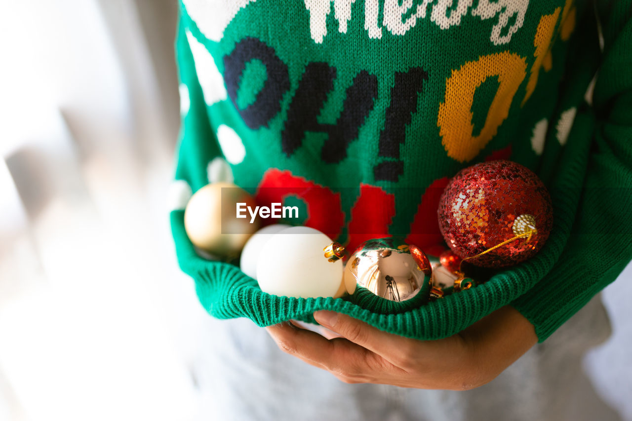 Midsection of woman carrying christmas ornament in sweater