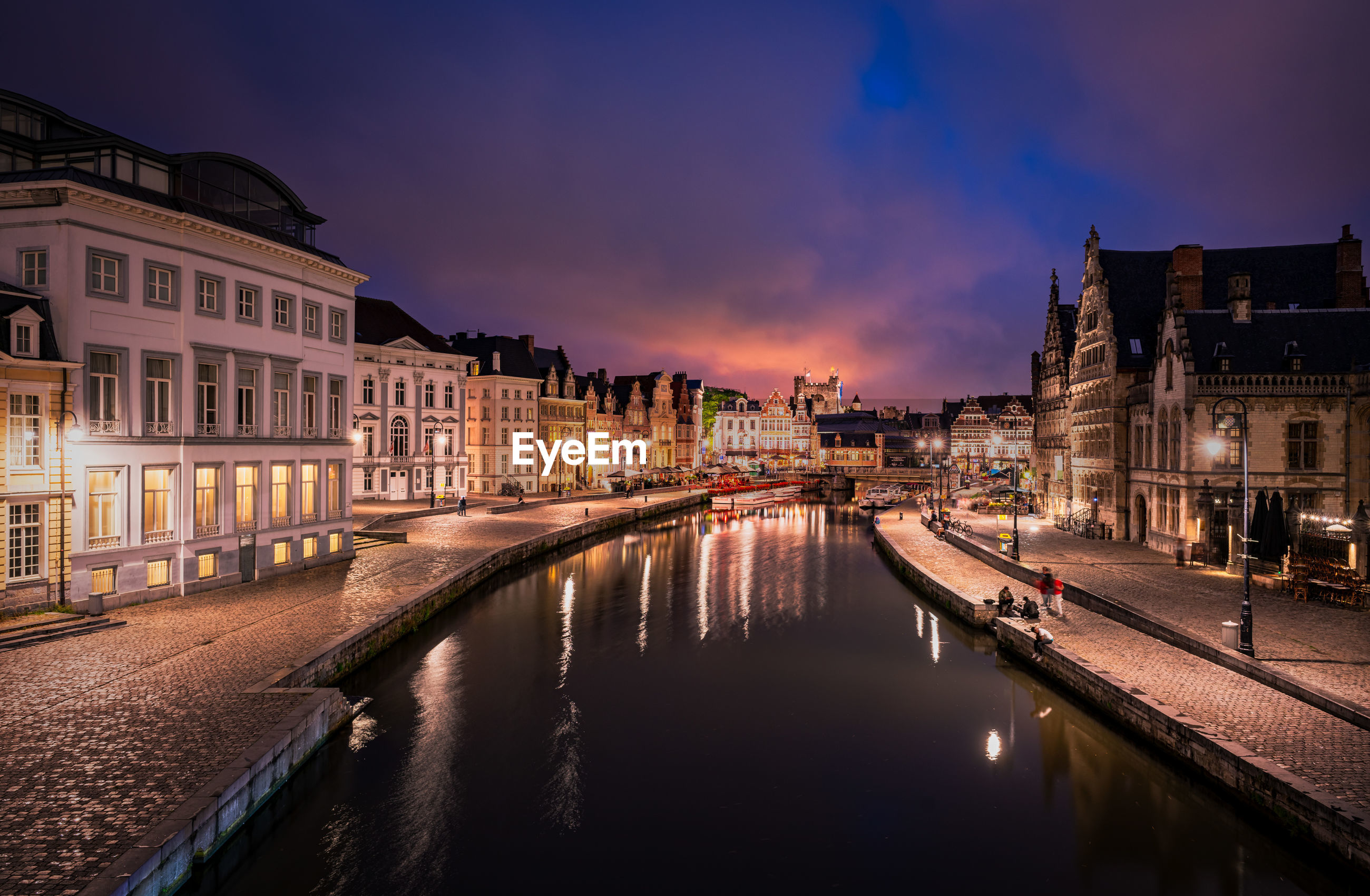 CANAL AMIDST ILLUMINATED CITY BUILDINGS AT NIGHT