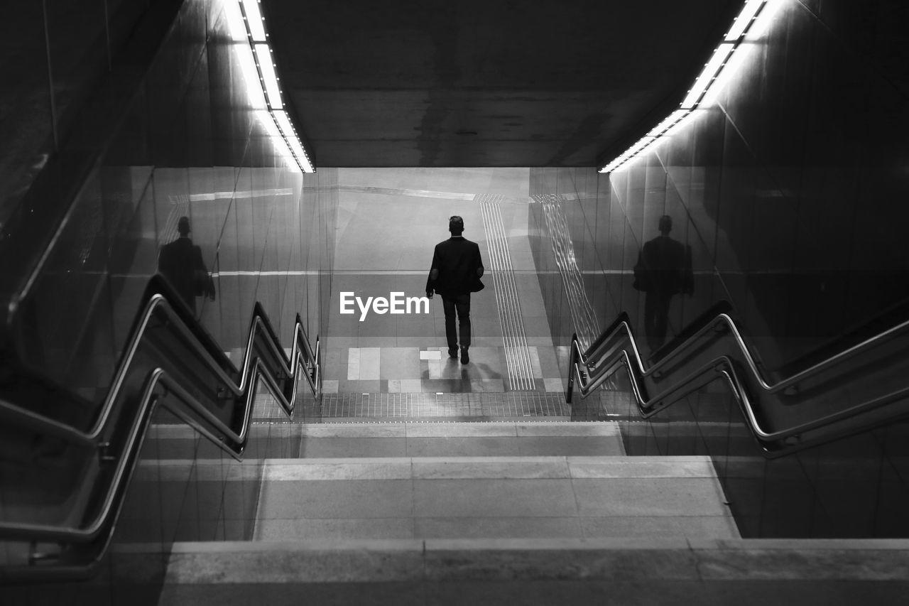 Rear view of man walking at subway station