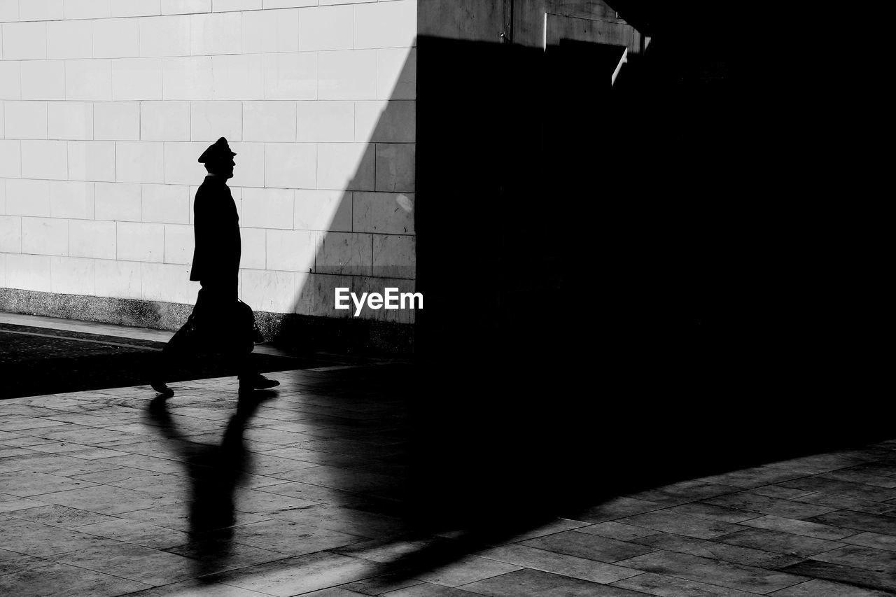 one person, real people, shadow, walking, architecture, full length, men, built structure, lifestyles, city, sunlight, silhouette, footpath, street, leisure activity, building exterior, wall - building feature, day, nature, outdoors, focus on shadow