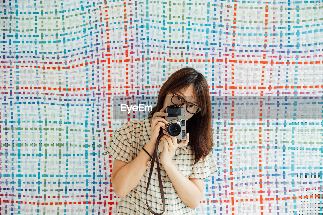 Portrait Of Mid Adult Woman Photographing With Camera Against Textile