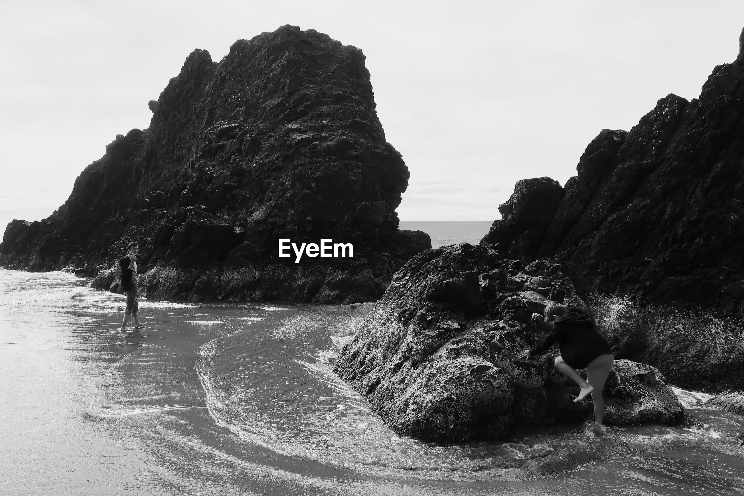 Man wading in sea against rock formations