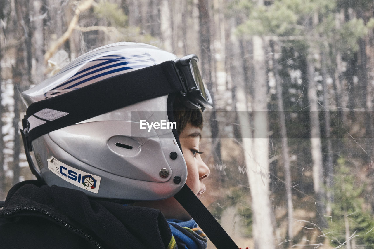 headshot, one person, portrait, child, focus on foreground, real people, childhood, forest, lifestyles, leisure activity, day, boys, tree, men, nature, land, winter, helmet, outdoors, innocence