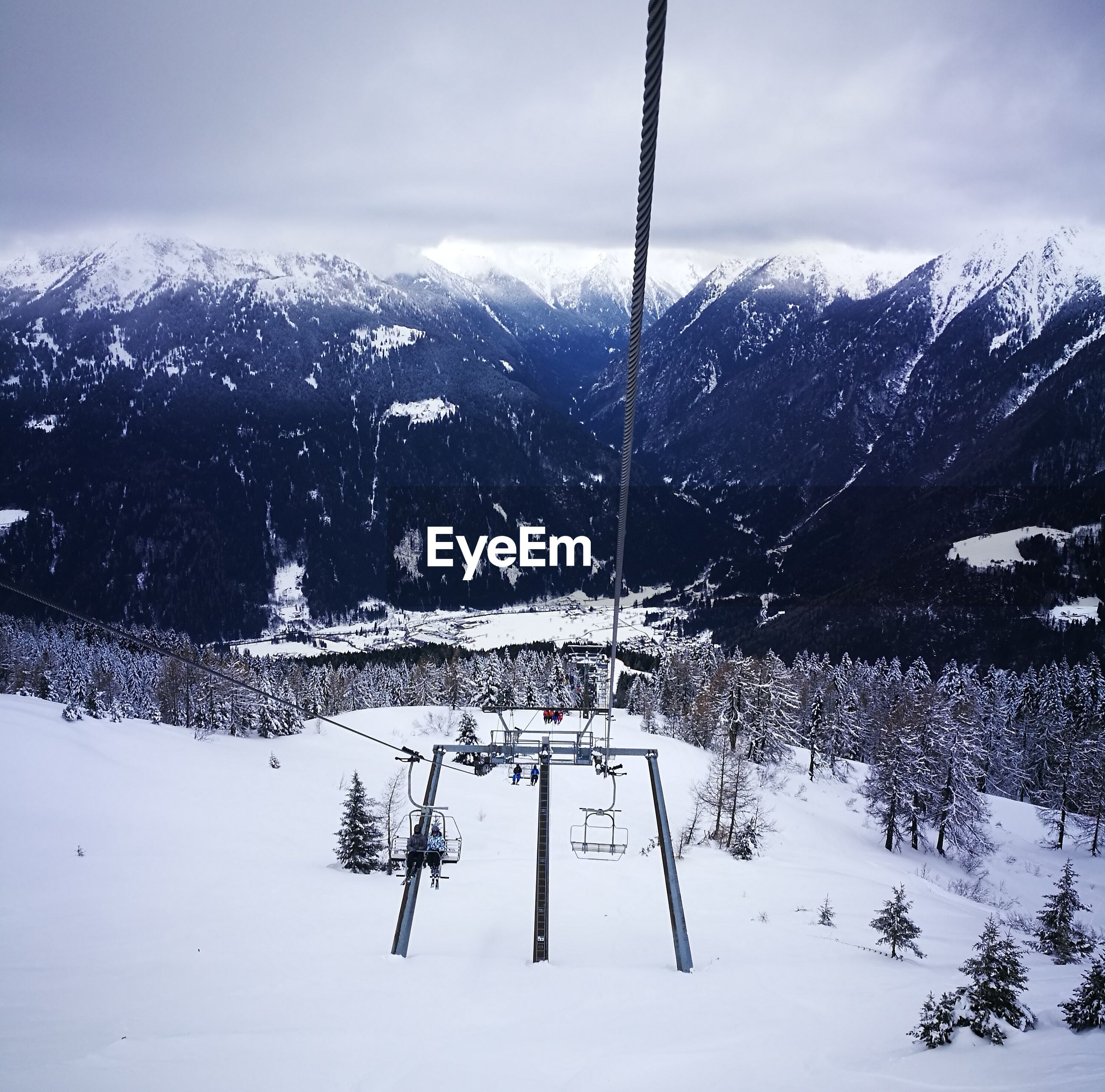 SKI LIFT OVER SNOWCAPPED MOUNTAIN AGAINST SKY