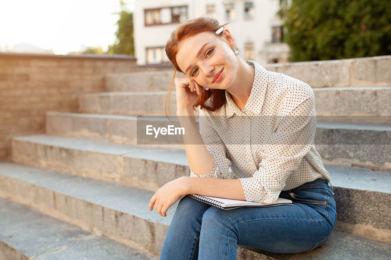 Woman holding book while sitting on steps