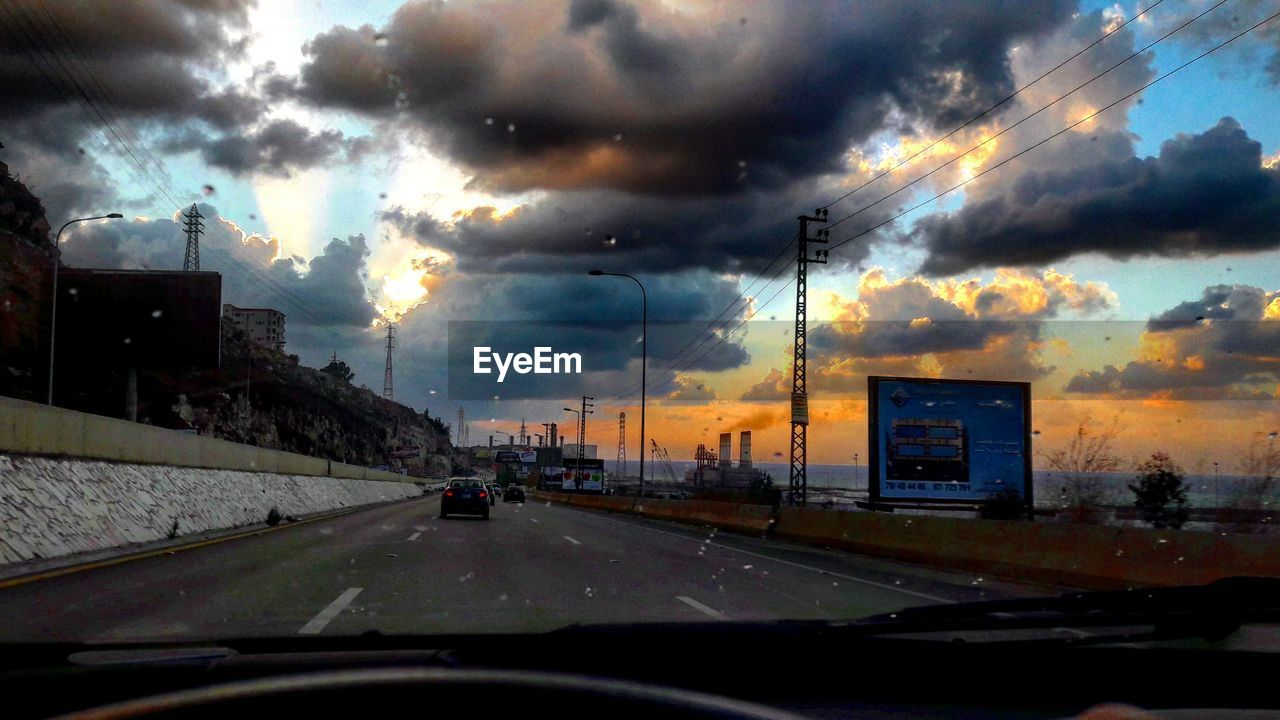 car, vehicle interior, land vehicle, transportation, cloud - sky, glass - material, car interior, windshield, sky, mode of transport, built structure, road, dramatic sky, architecture, car point of view, storm cloud, sunset, no people, city, building exterior, nature, thunderstorm, outdoors, day
