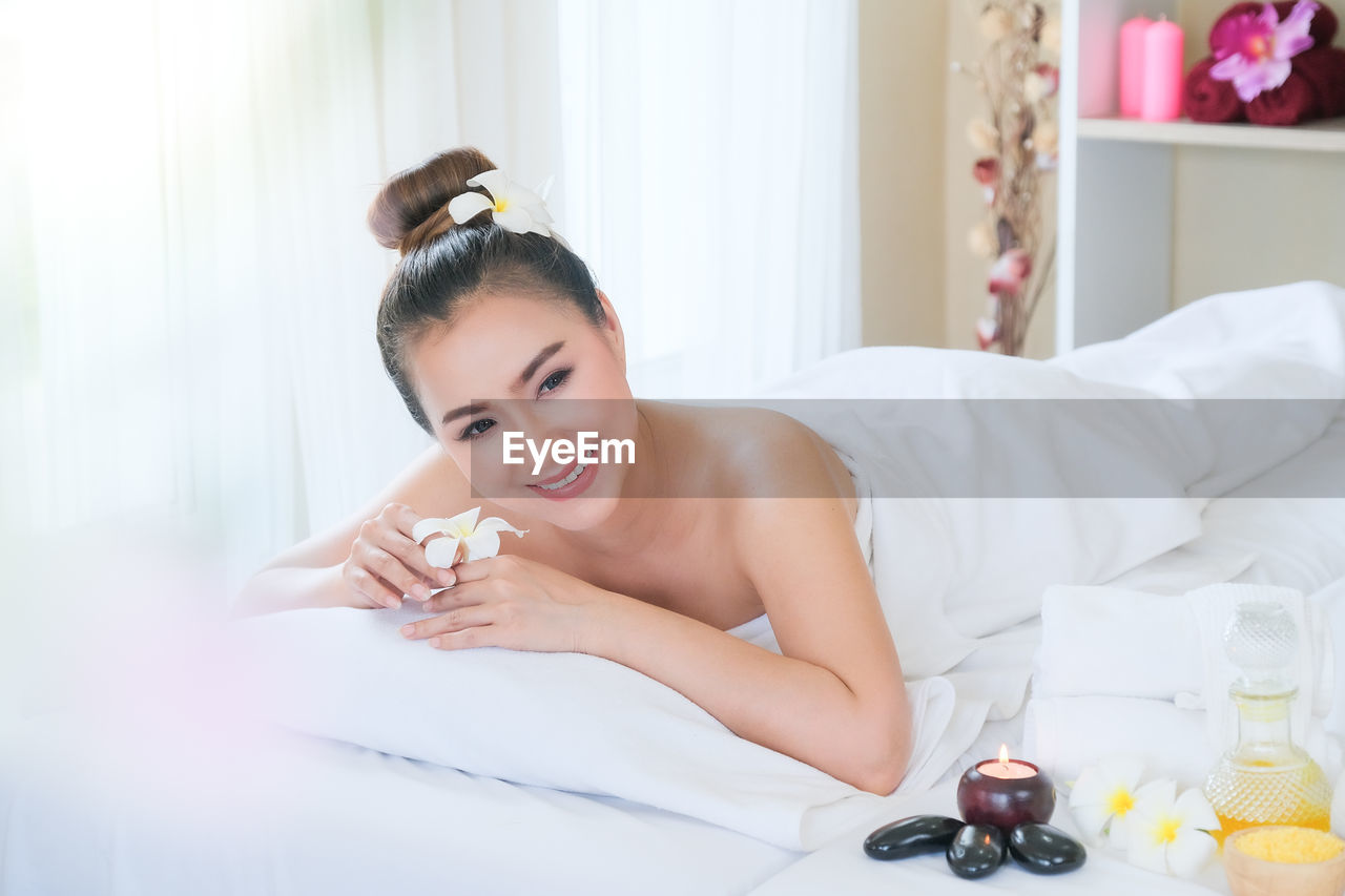 YOUNG WOMAN LYING DOWN ON BED IN KITCHEN
