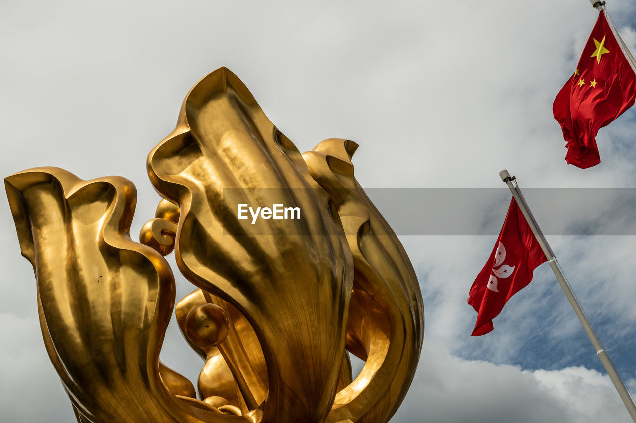 LOW ANGLE VIEW OF GOLDEN STATUE AGAINST SKY