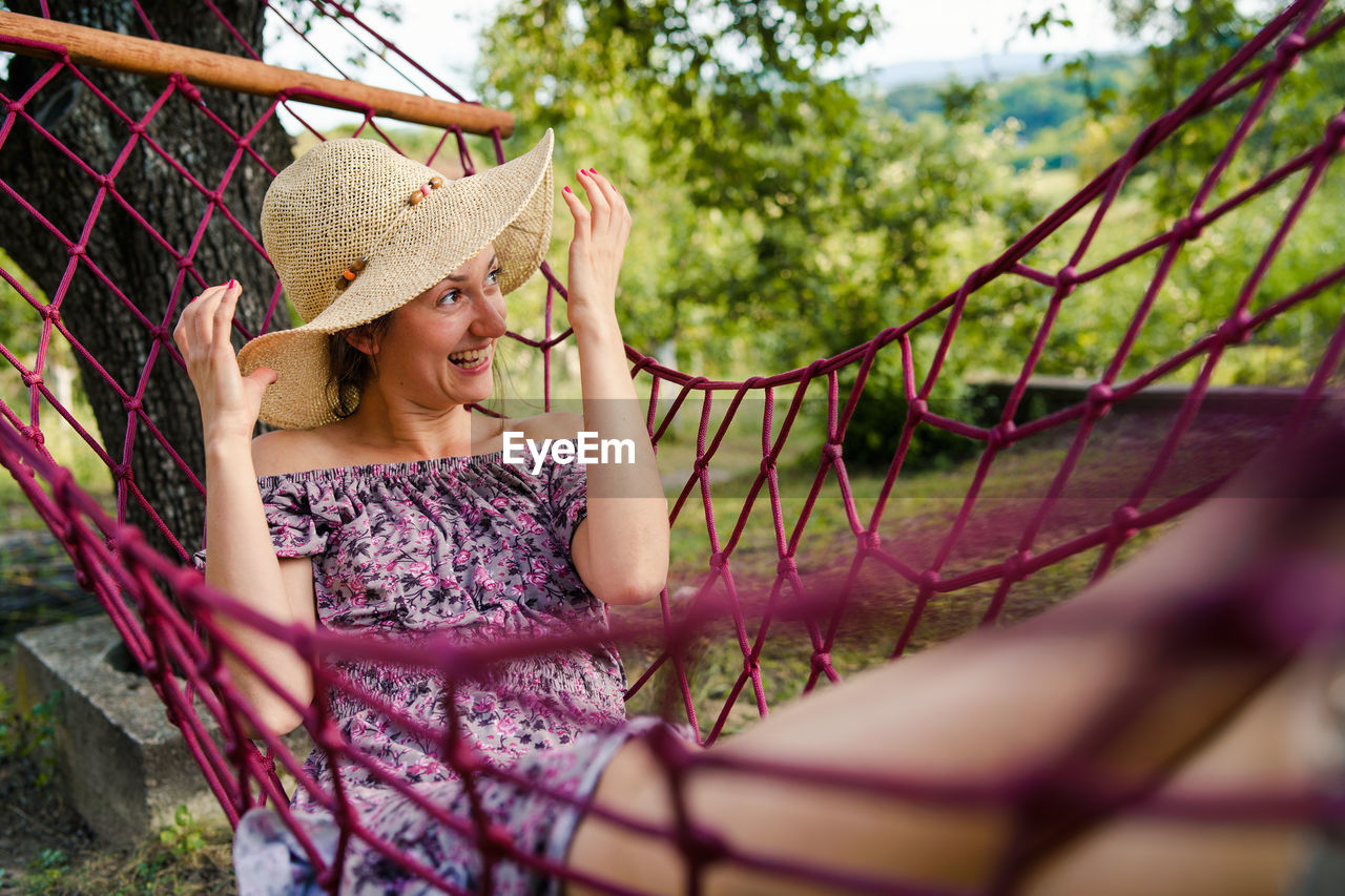 hat, one person, women, leisure activity, adult, clothing, real people, lifestyles, selective focus, plant, casual clothing, day, young adult, young women, front view, three quarter length, sun hat, growth, outdoors, hairstyle, beautiful woman