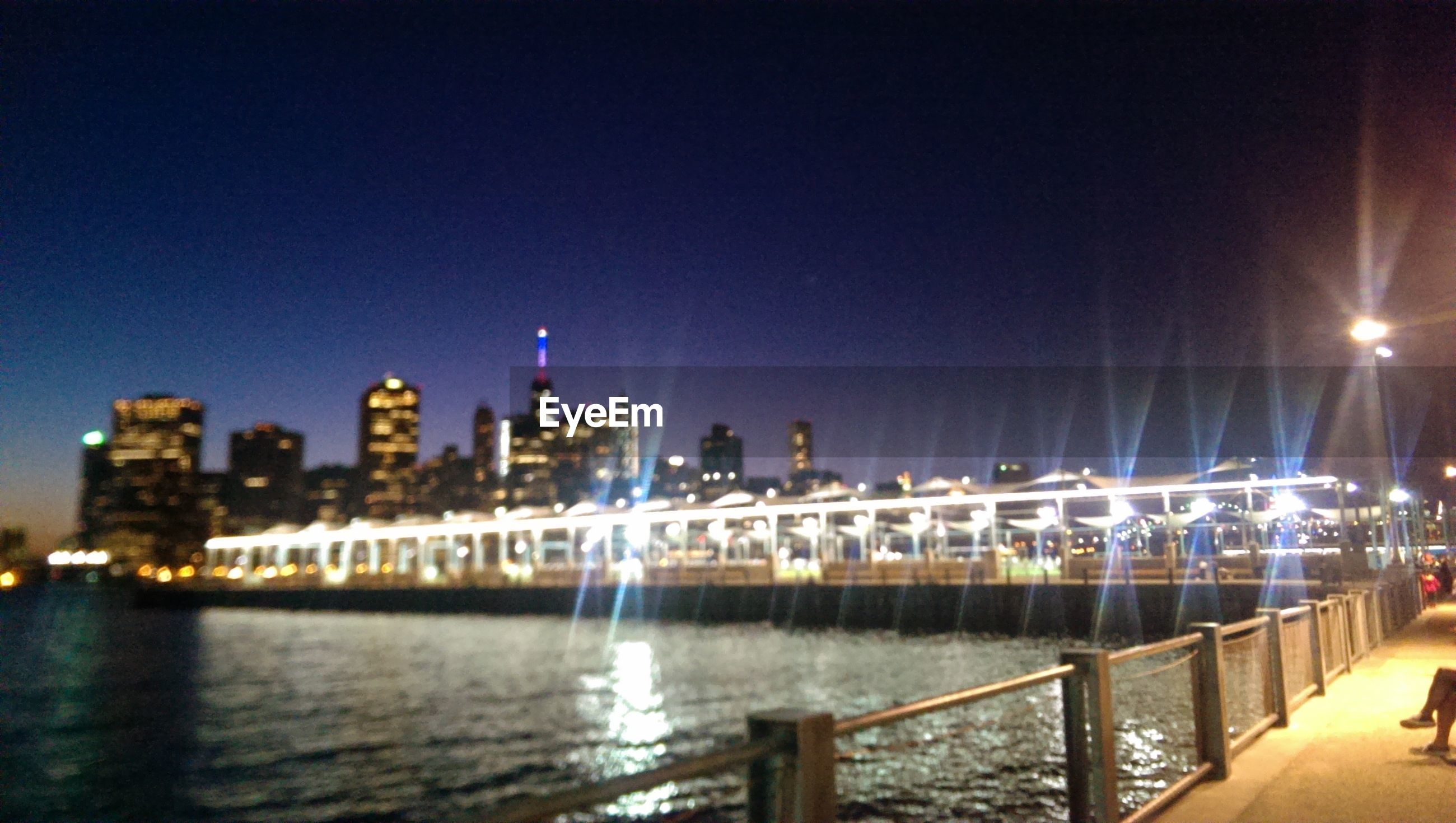 illuminated, night, architecture, water, built structure, building exterior, city, river, clear sky, reflection, cityscape, waterfront, skyscraper, railing, lighting equipment, modern, copy space, urban skyline, travel destinations, blue