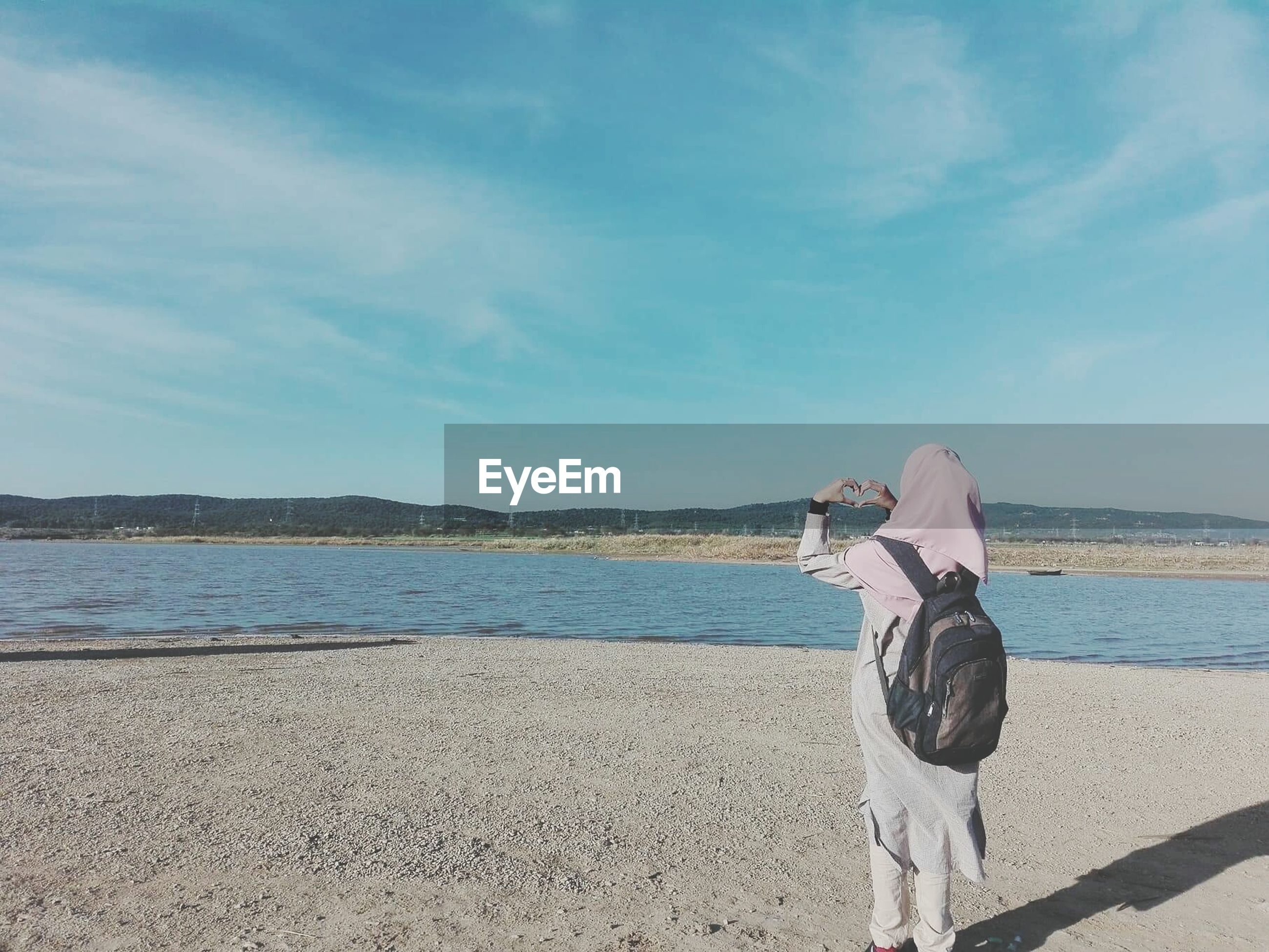 Rear view of woman with backpack looking at sea against sky