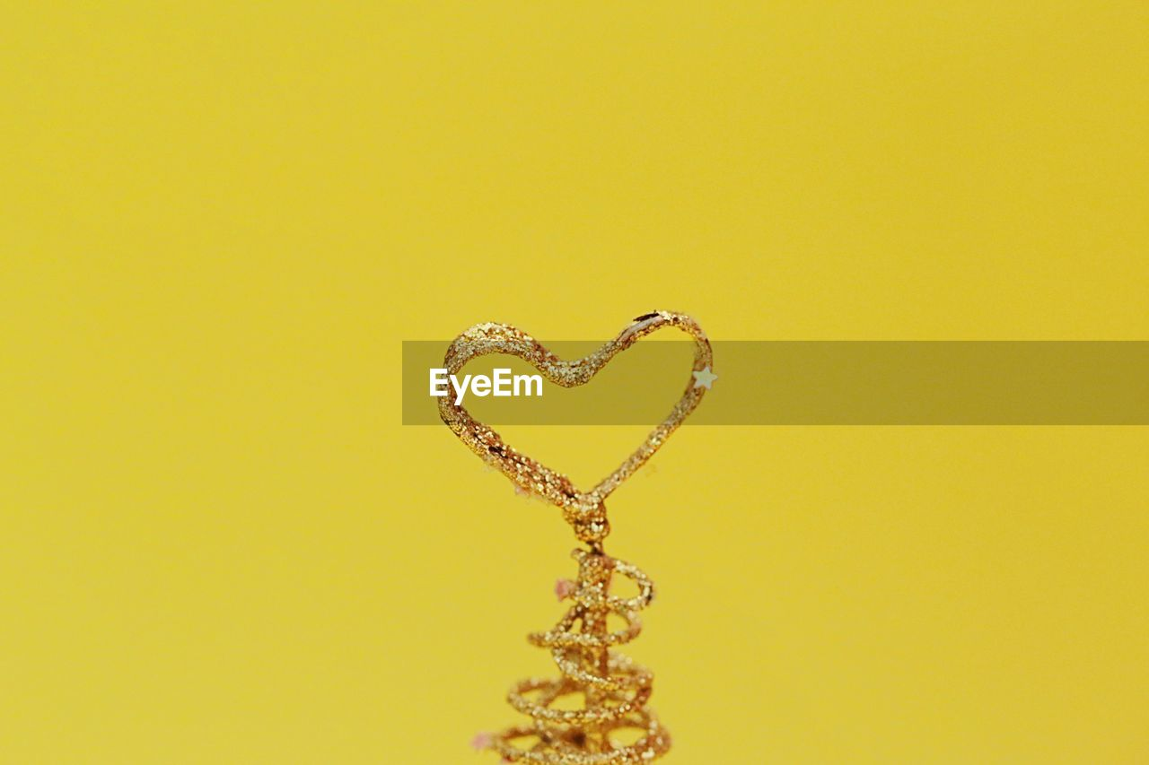 heart shape, copy space, no people, necklace, indoors, positive emotion, love, studio shot, jewelry, still life, emotion, close-up, yellow, art and craft, gold colored, colored background, creativity, wealth, gold, single object, luxury, personal accessory, silver colored, valentine's day - holiday