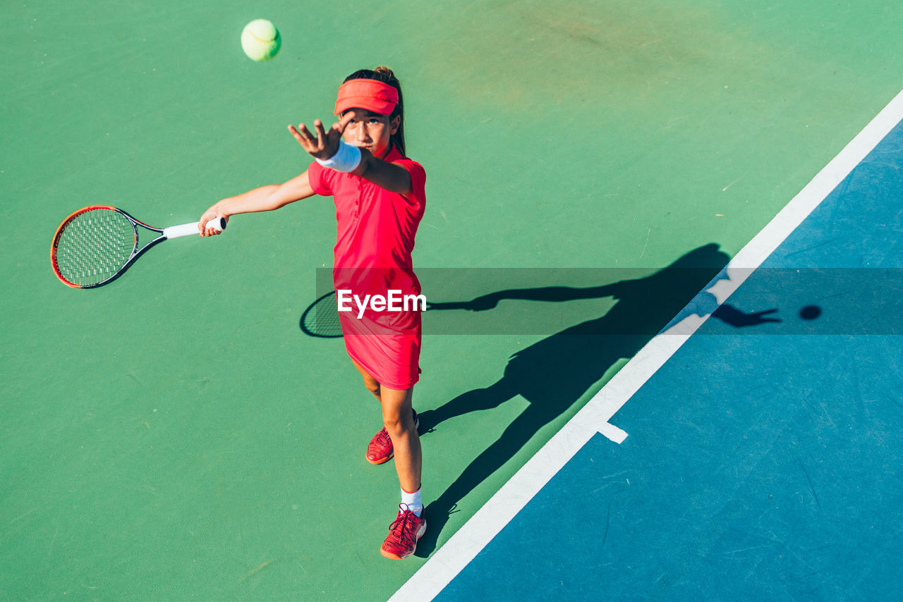 High angle view of girl practicing tennis while standing in court during sunny day