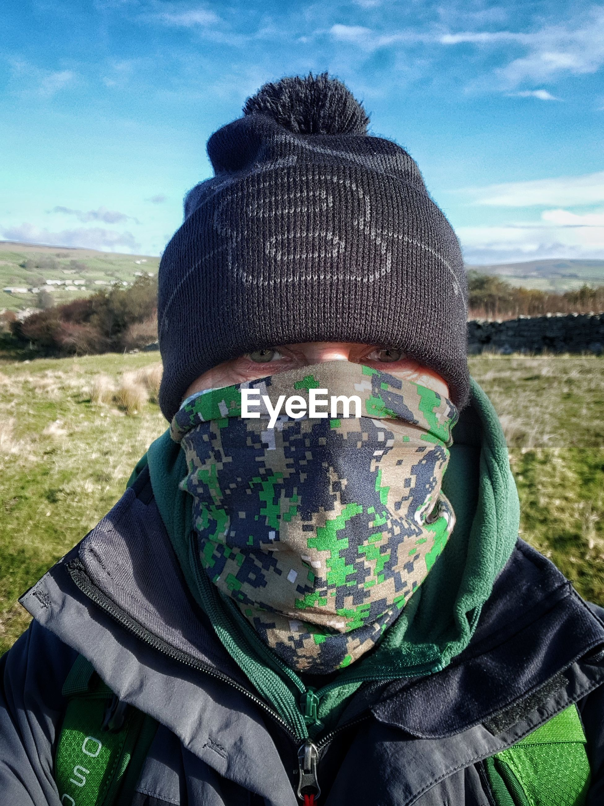 portrait, one person, headshot, sky, land, field, real people, day, nature, green color, leisure activity, clothing, lifestyles, cloud - sky, men, close-up, front view, landscape, obscured face, outdoors, warm clothing, human face