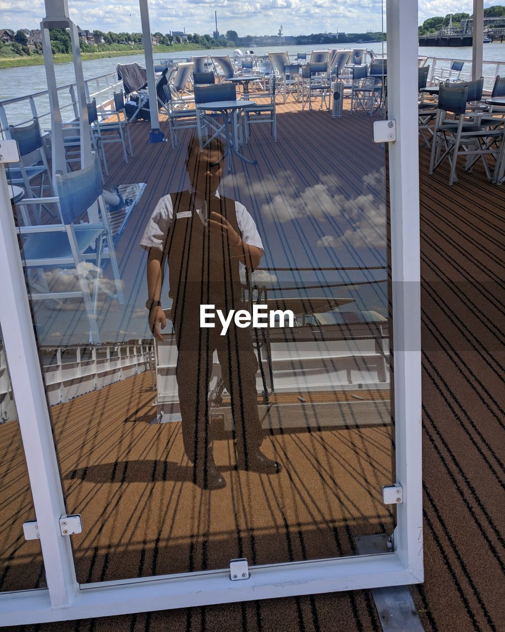 Full length of man reflecting in glass window in boat