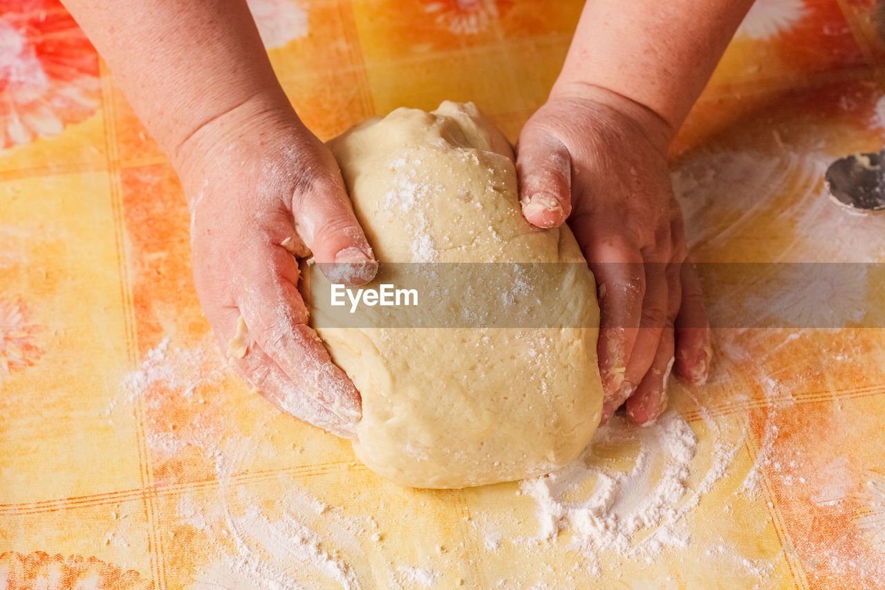 Close-Up Of Woman Kneading Dough At Table