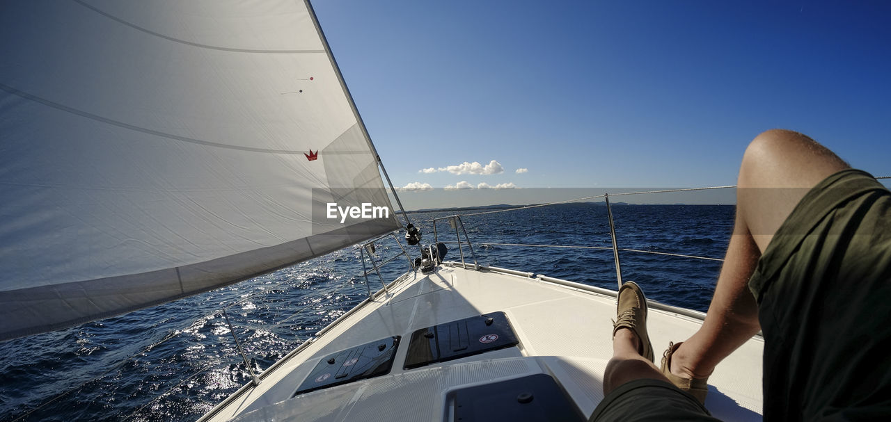 sea, sailing, sailboat, nautical vessel, summer, yacht, activity, yachting, aquatic sport, real people, beauty in nature, sailing ship, nature, outdoors, boat deck, regatta, water, one person, horizon over water, day, people