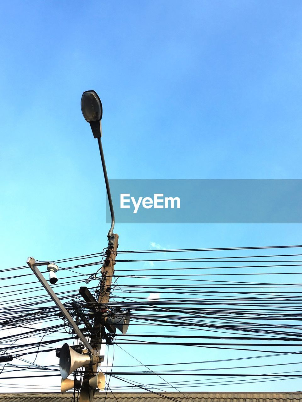 Low angle view of telephone pole with street light against blue sky