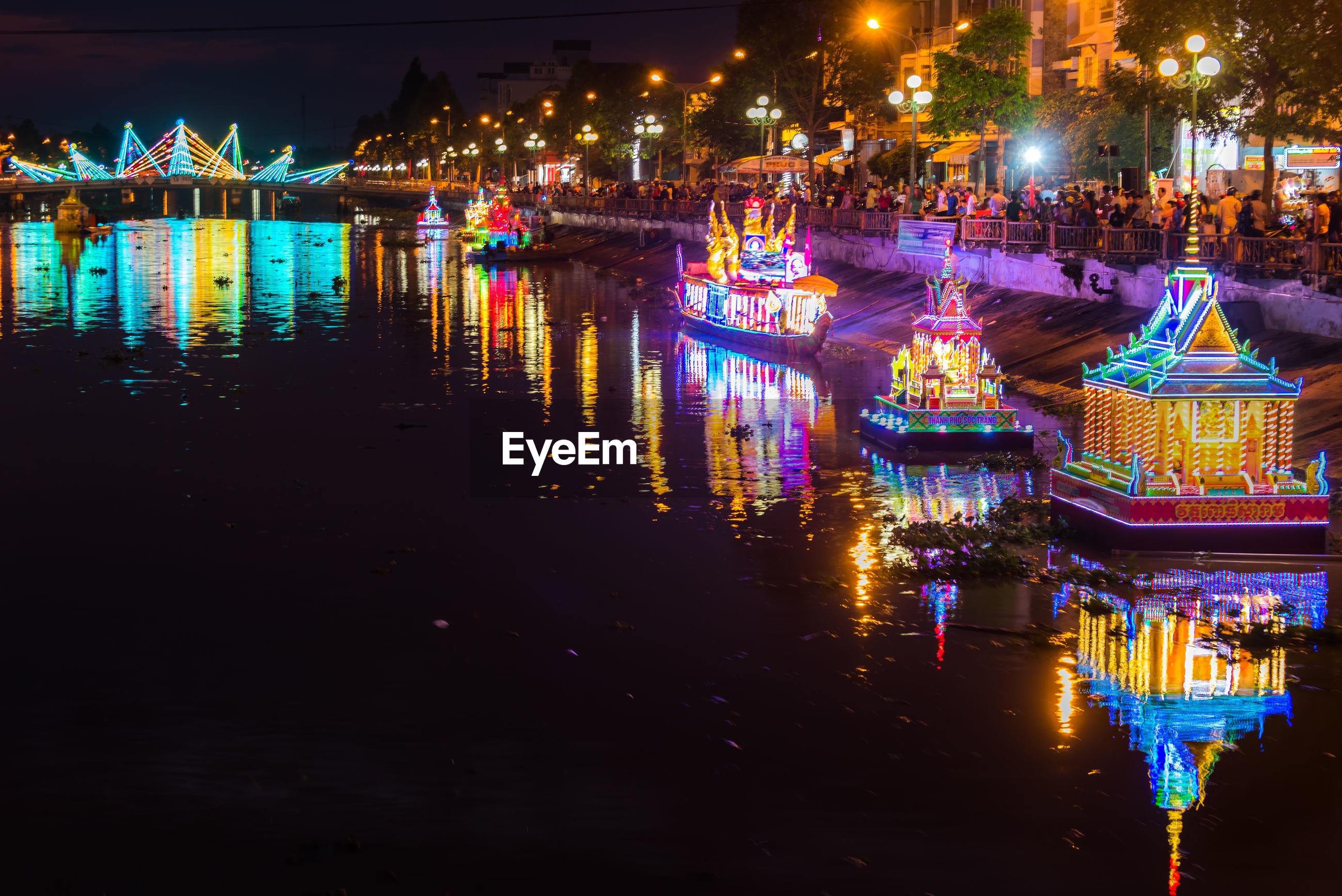 Illuminated buildings by river in city at night soc trang