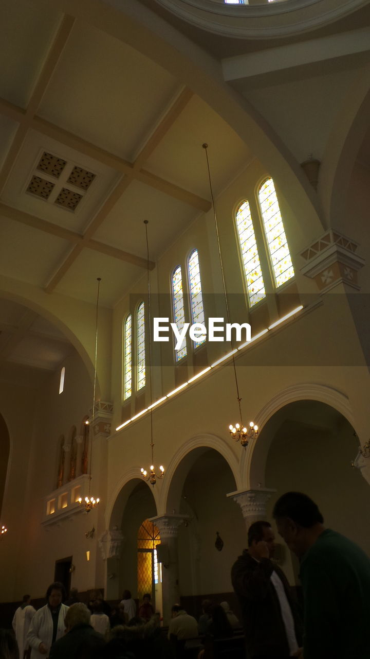 indoors, religion, arch, place of worship, real people, architecture, built structure, ceiling, spirituality, women, men, window, architectural column, low angle view, lifestyles, large group of people, pew, day, people