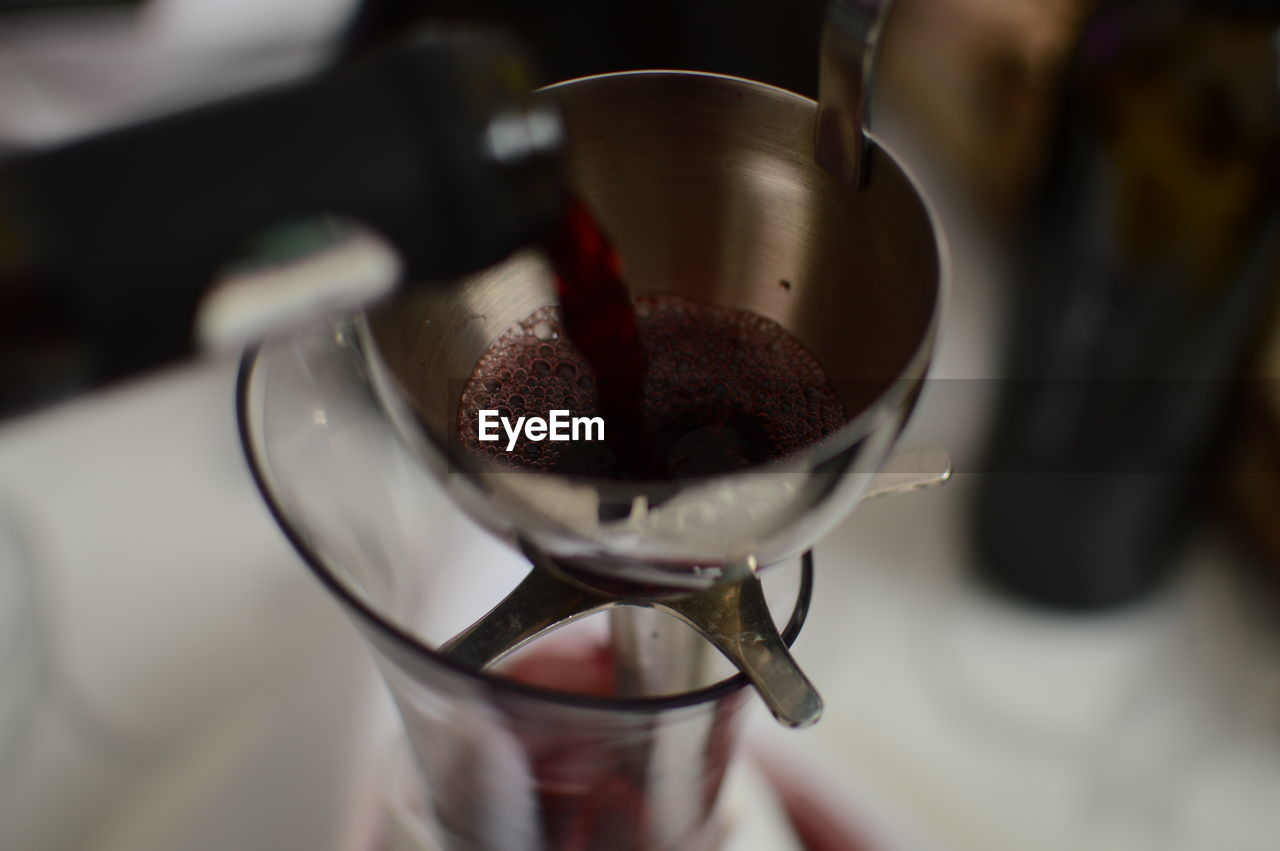 Cropped bottle pouring wine in glass from strainer