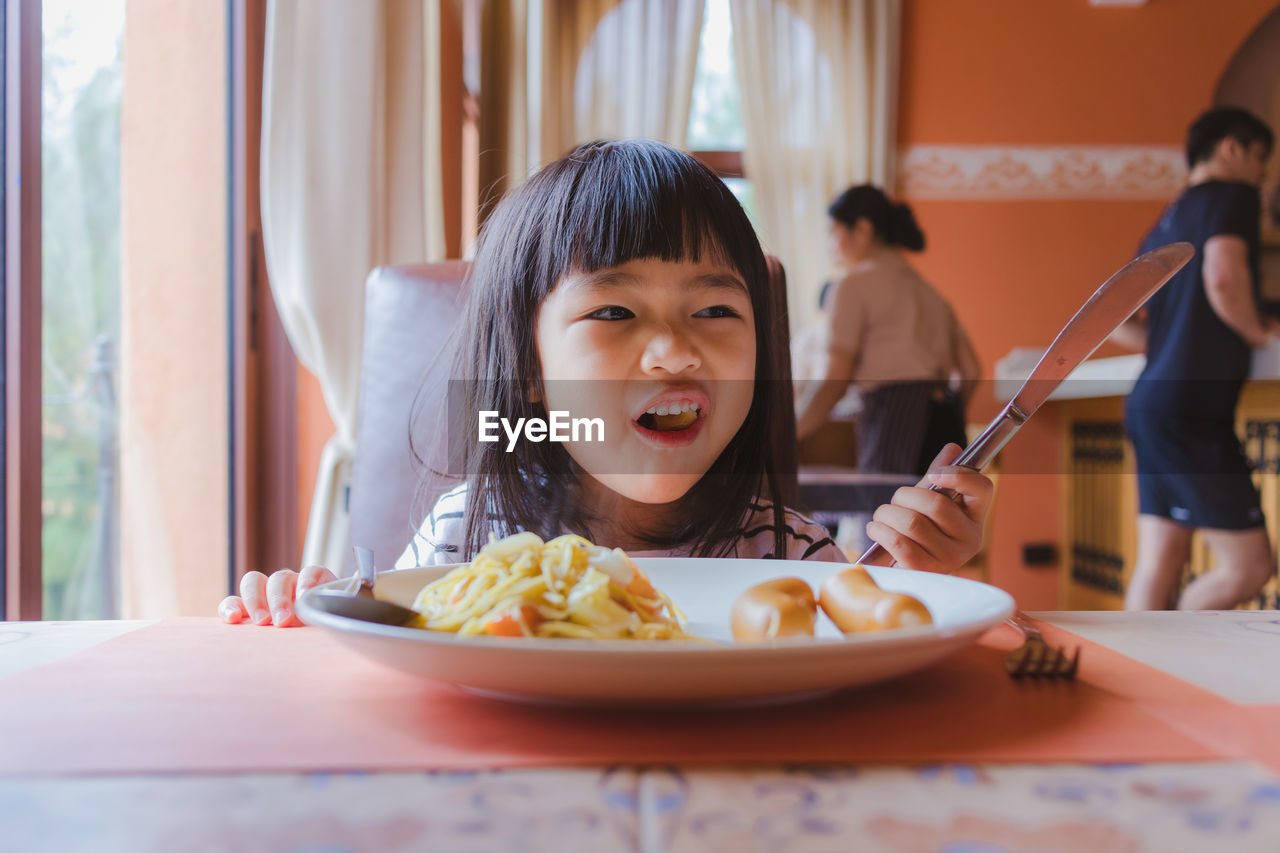 Close-up of girl holding knife while sitting at table in restaurant