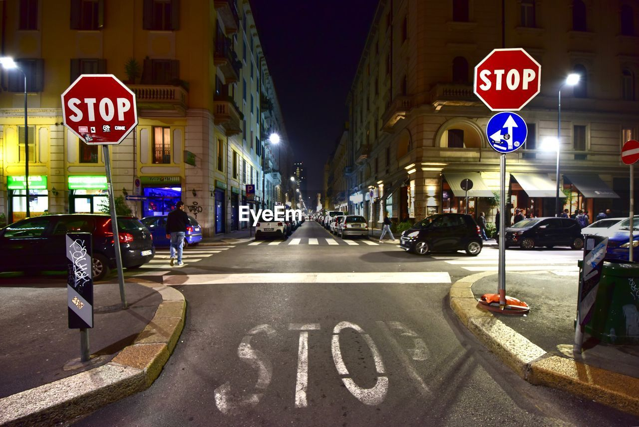 sign, city, architecture, text, communication, road, western script, building exterior, built structure, street, road sign, car, transportation, illuminated, stop sign, road marking, night, information, motor vehicle, symbol, guidance, outdoors