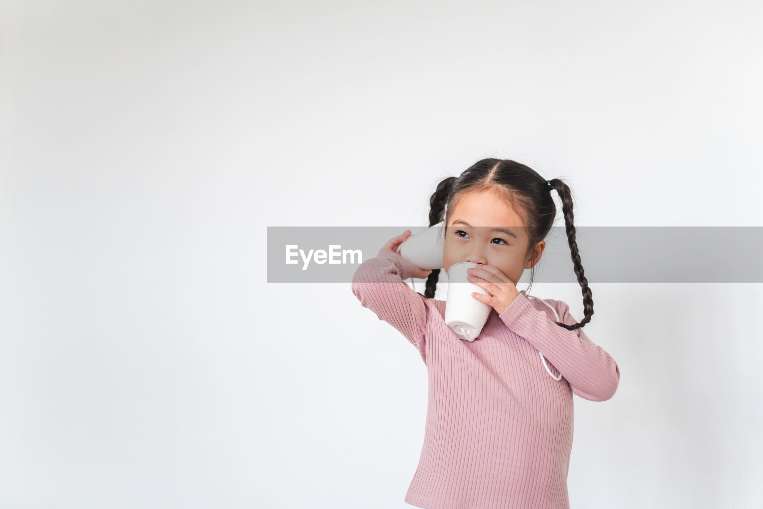 Smiling girl holding cup phone while standing against white background
