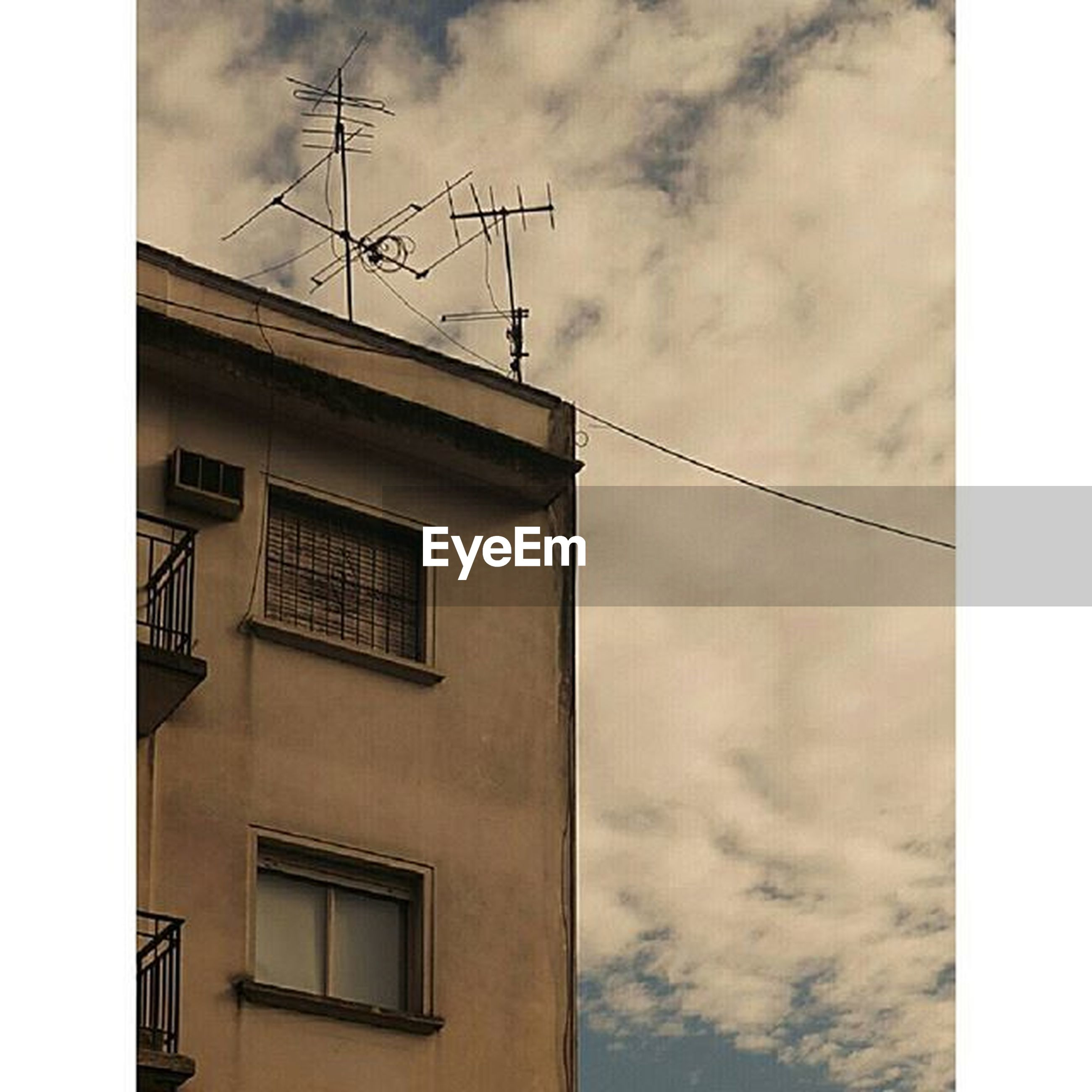 transfer print, low angle view, sky, architecture, built structure, building exterior, power line, auto post production filter, cloud - sky, power supply, fuel and power generation, cable, technology, electricity, cloudy, cloud, connection, electricity pylon, day, outdoors
