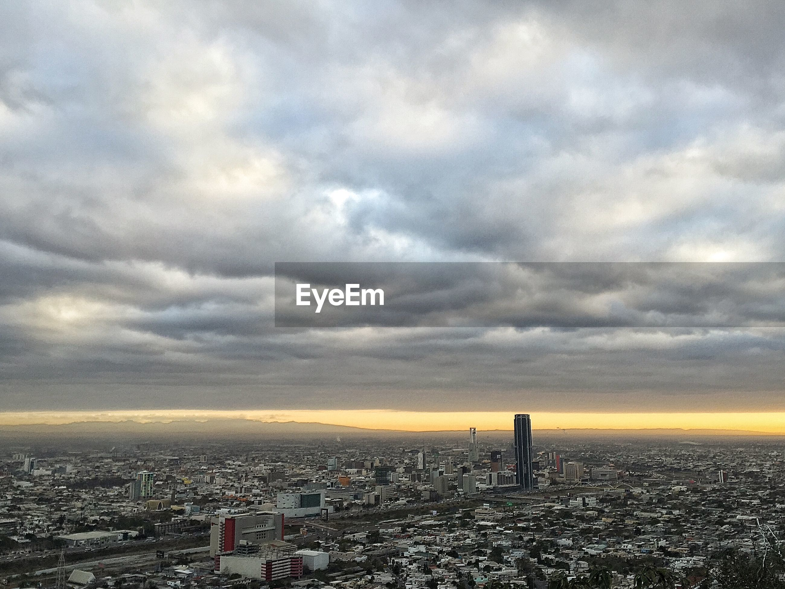 Aerial view of cityscape under cloudy sky