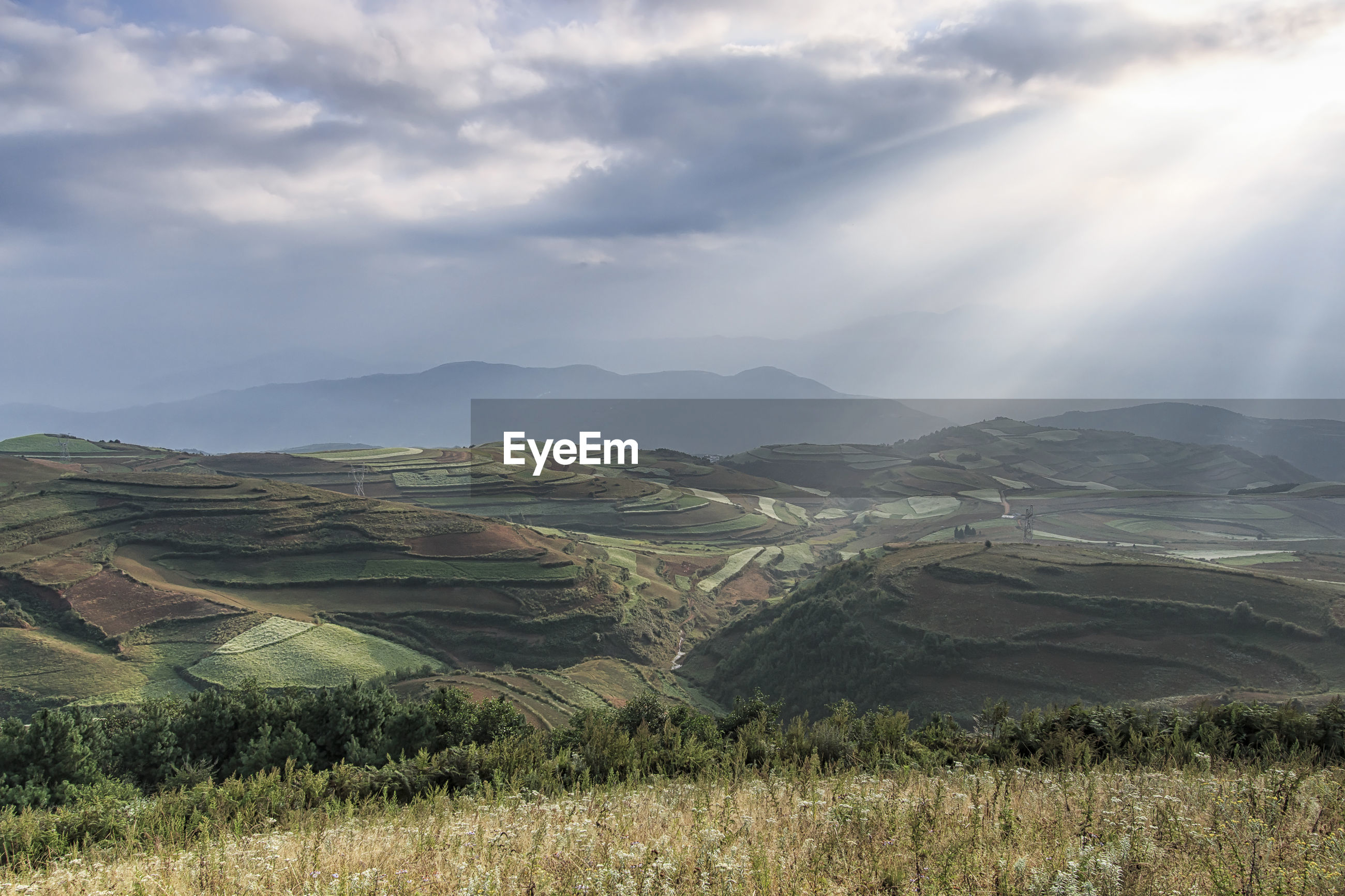 Scenic view of landscape against cloudy sky and sunbeam