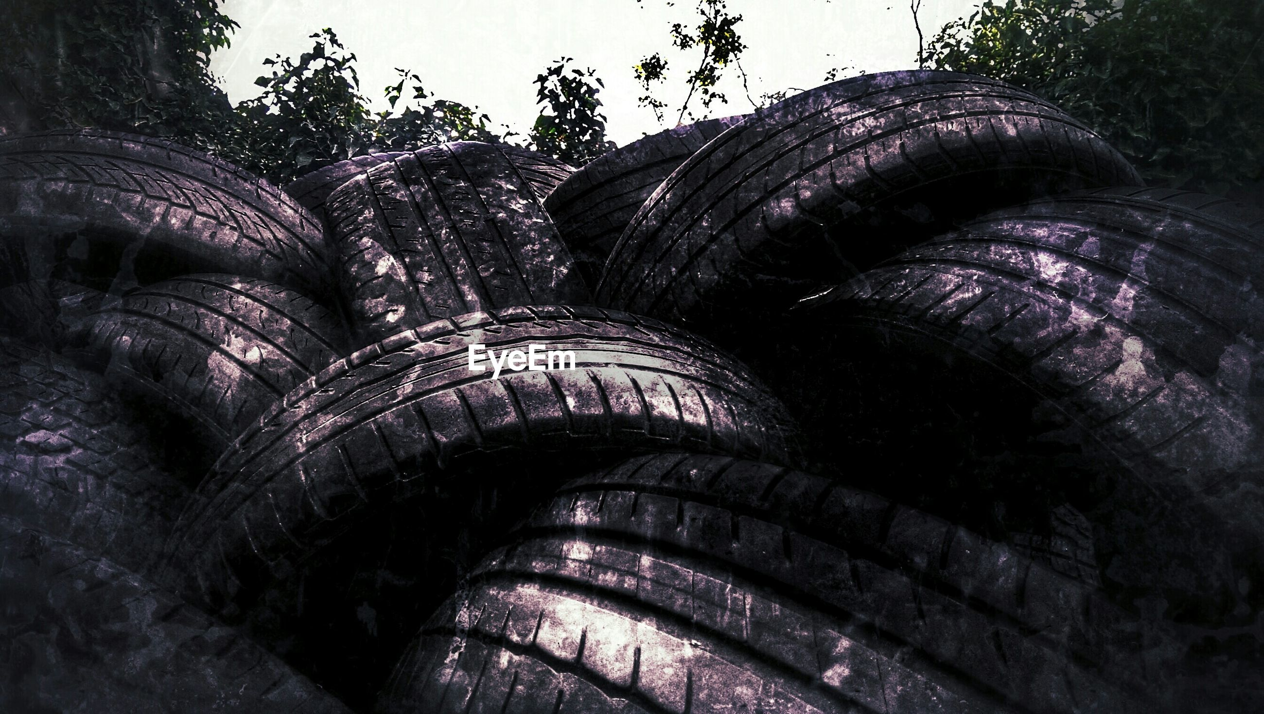 Stack of old abandoned tires against clear sky